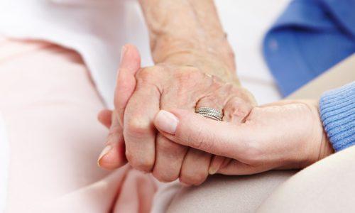 Pflegerin hält Seniorin an der Hand